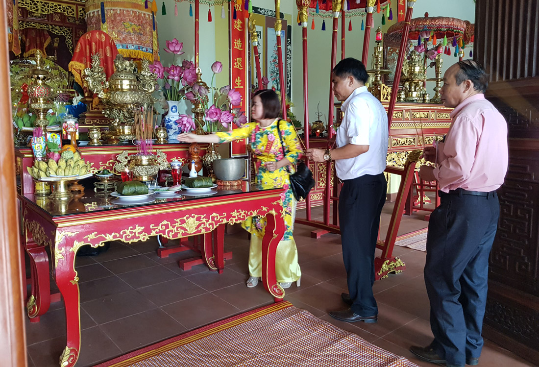 Visitors offer incense to commemorate Hung Kings at the temple located in the tourism village