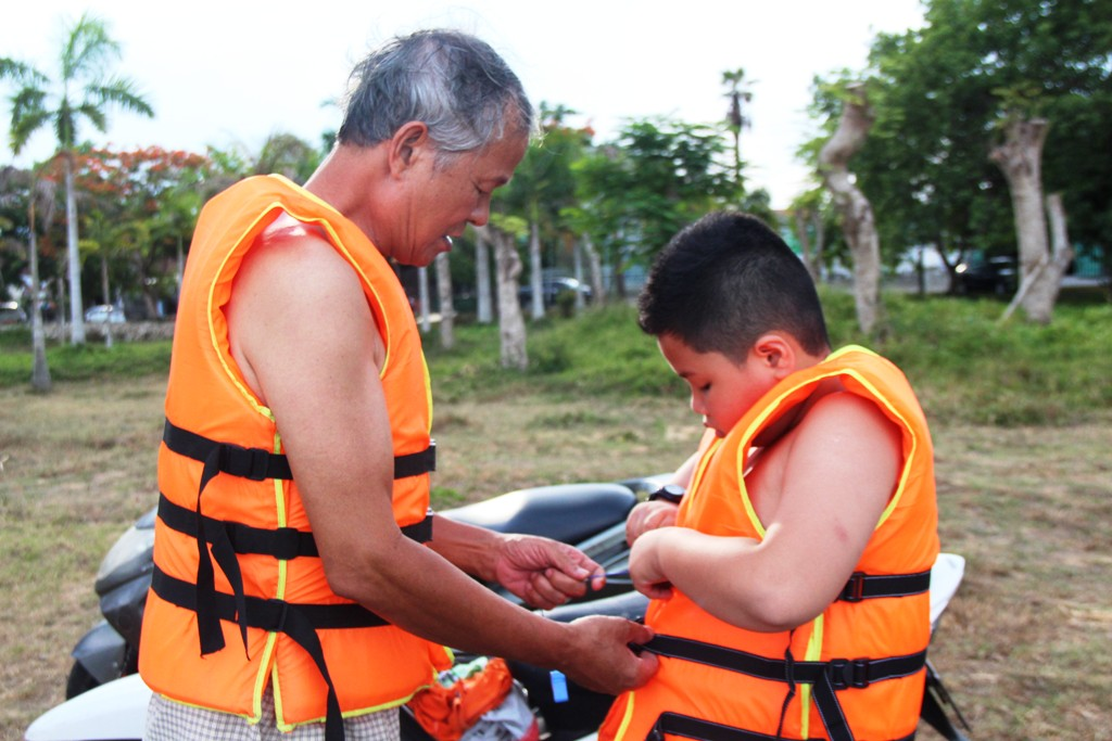 The old man wearing a life jacket for his grandchildren before joining into the cool water