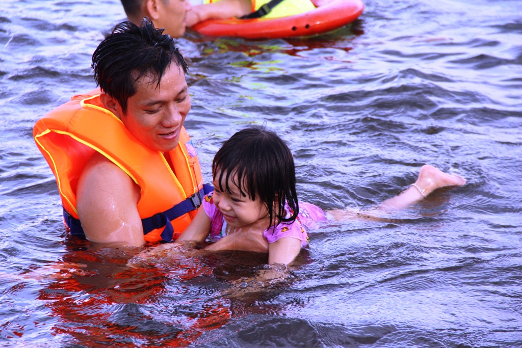 Meanwhile, a little girl looks happy when her father teaches her to swim