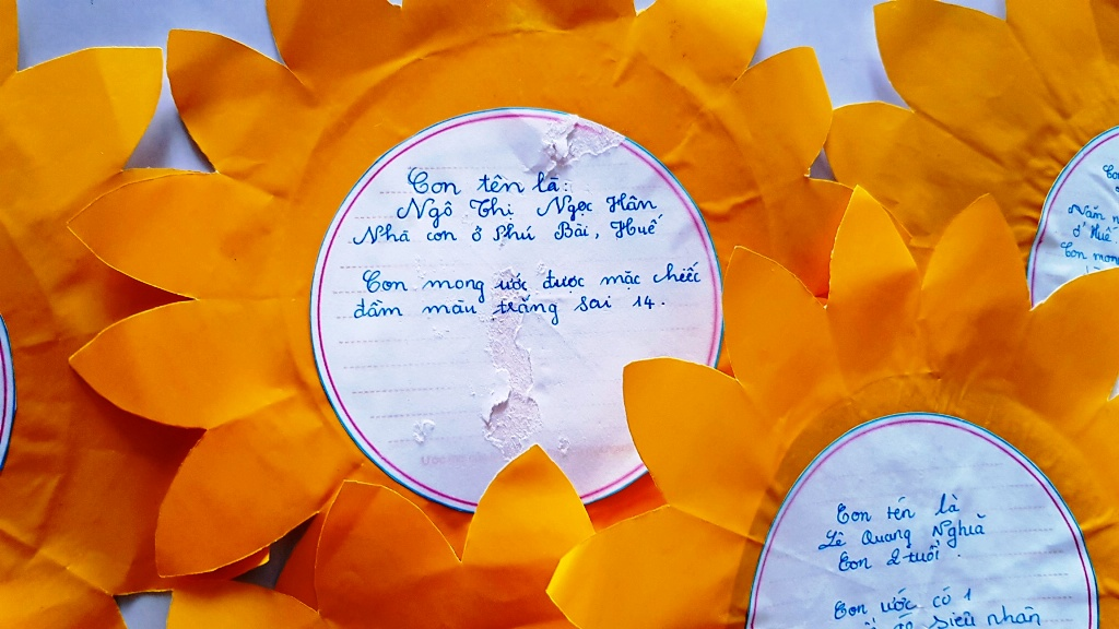 Ngọc Hân, a child patient, expresses her simple wish on a sunflower: owning a white dress