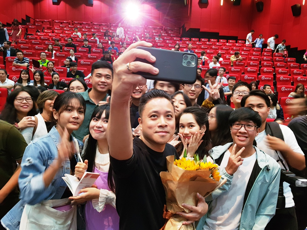Victor Vu, the director of the film Dreamy Eyes taking a photo with fans