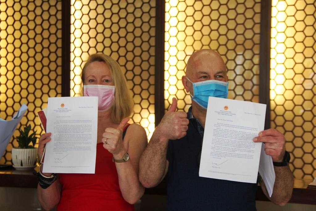 Two foreign tourists giving thumbs up sign to show their satisfaction when receiving a letter from Chairman of Provincial People's Committee Phan Ngoc Tho after the quarantine.