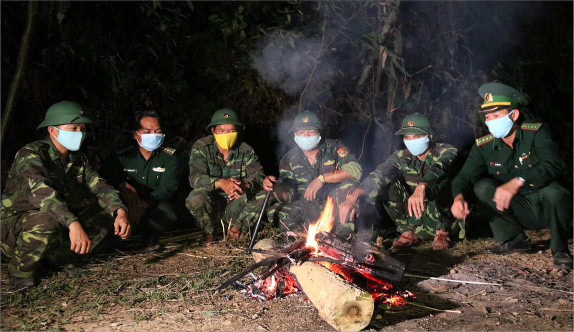 In the cold late-night, the soldiers warm up by the fire while on duty