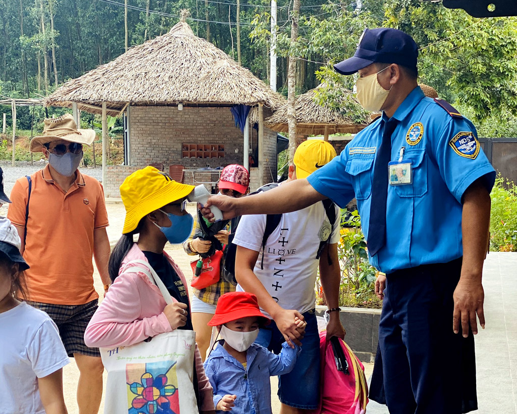 Checking body temperature of tourists before entering Bach Ma Village Spring Resort
