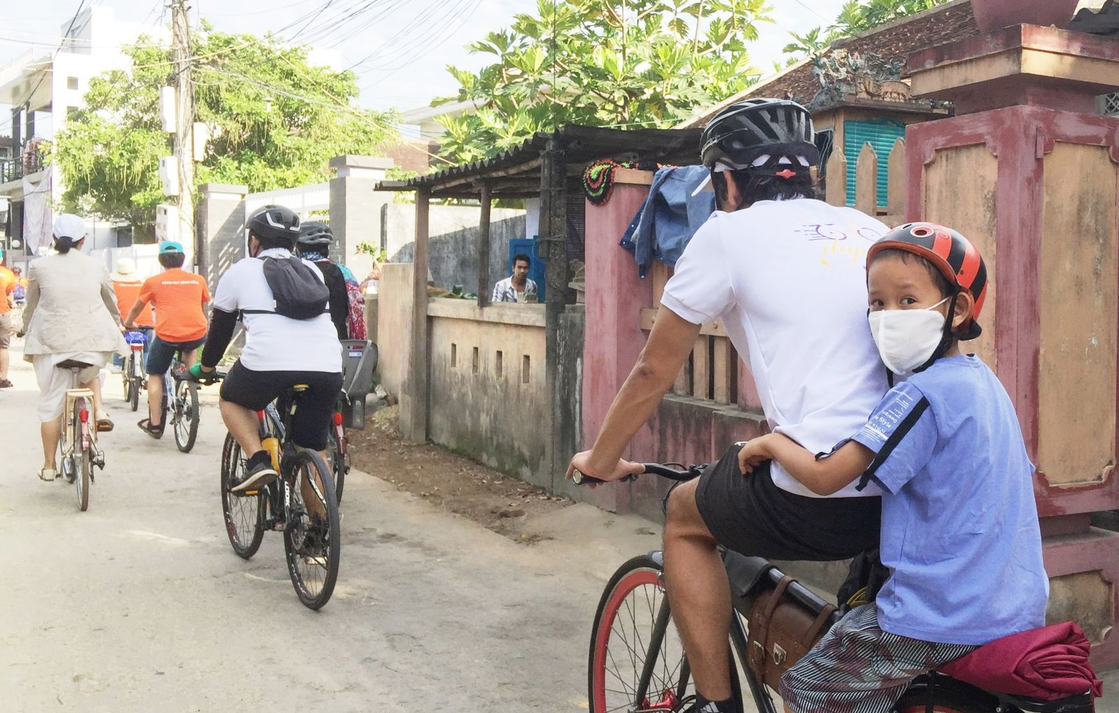 Although some children cannot cycle by themselves, they still go with their father in calling for environmental protection