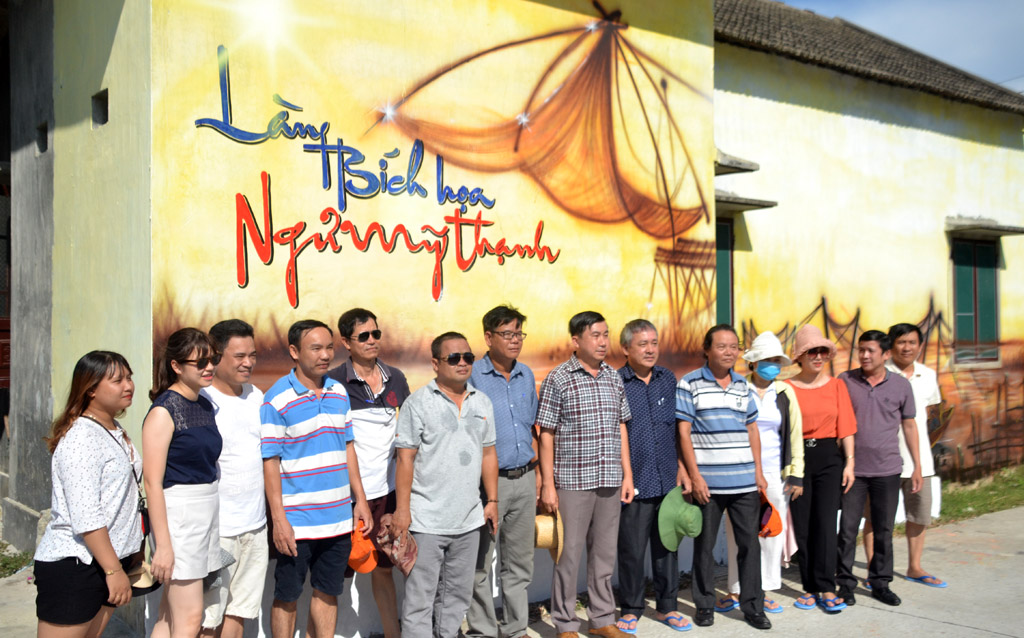 The delegation taking a souvenir photo on the side of Ngu My Thanh fresco street