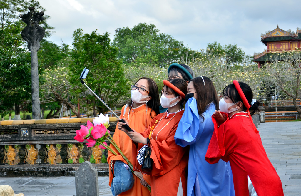 A group of young tourists from Hanoi wearing five-panel ao dai and having their photos shot in the Imperial City