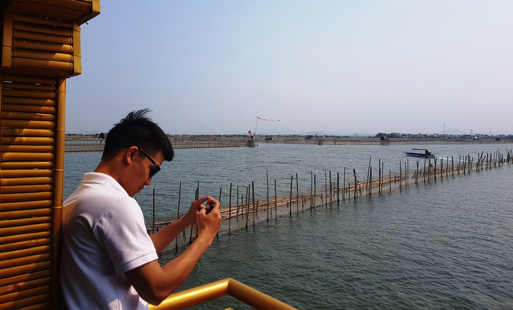 A young guy taking photos of Chuon lagoon in the late afternoon