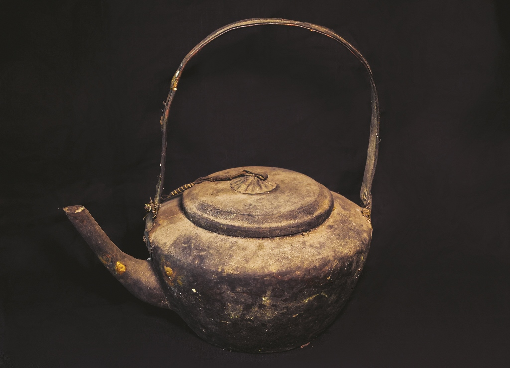 The kettle made of flattened bronze with high curved handle to avoid hot burn
