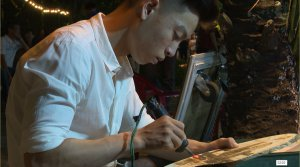 Portrait with fire pen attracts visitors on pedestrian street