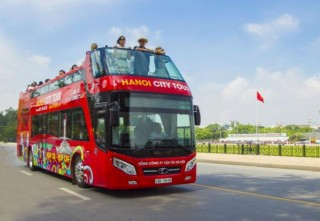 Piloting convertible double decker bus to carry tourists in Hue
